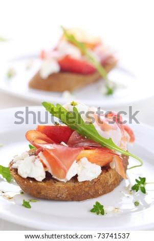 Sandwich with ham, fresh peach and soft goat cheese on white plate