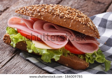 Sandwich with ham, lettuce and tomatoes on an old table. horizontal  - stock photo