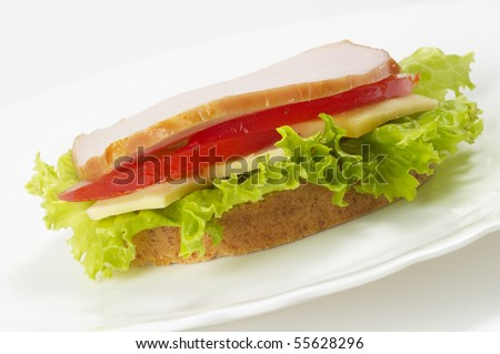Sandwich with ham, tomato and cheese over white plate