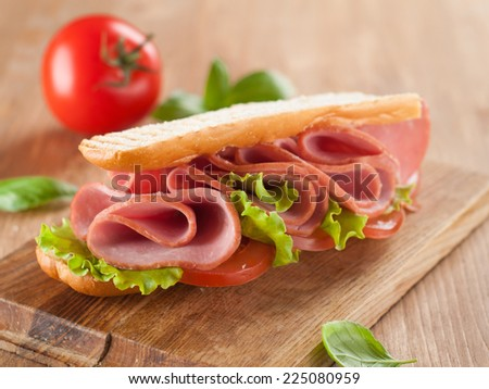 Sandwich with ham,tomato and lettuce on the wooden cutting board, selective focus - stock photo