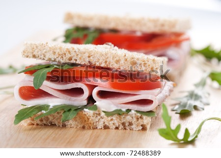 Sandwich with ham,tomato, and rucola salad on the wooden cutting board - stock photo