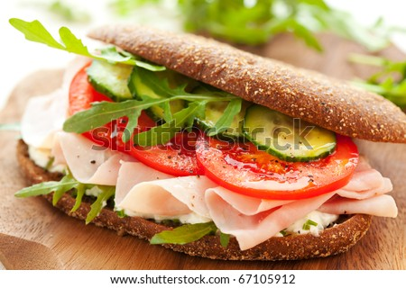 Sandwich with ham,tomato, cucumber and arugula on the wooden cutting board