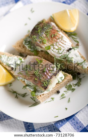 Sandwich with herring and white sauce decorated slice of lemon