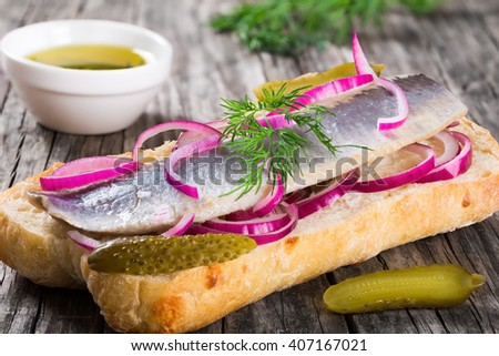 sandwich with herring fillets, onion, pickled cucumber and dill on parchment paper on an oval dish on an old rustic table, traditional street food in Norway, close-up - stock photo