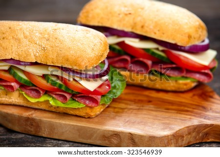 Sandwich with lettuce, slices of fresh tomatoes, cucumber, red onion, salami and cheese. - stock photo
