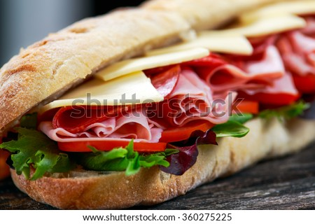 Sandwich with lettuce, slices of fresh tomatoes, salami, hum and cheese - stock photo