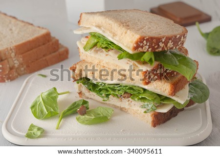sandwich with mayonaisse, turkey, cheese and fresh spinach on white chopping board