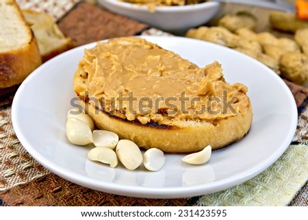 Sandwich with peanut butter in a plate with nuts on a napkin, bread on a wooden boards background - stock photo