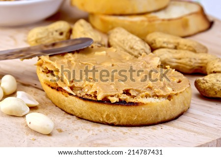 Sandwich with peanut butter, nuts, and a knife on a wooden boards background - stock photo