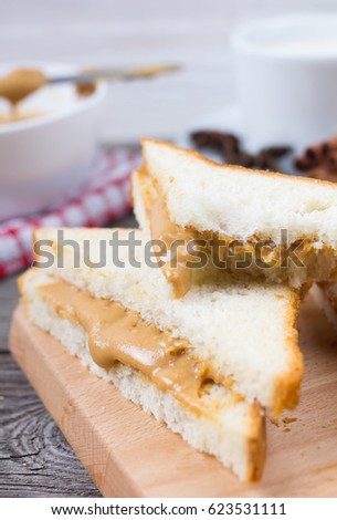 Sandwich with peanut paste, and a cup of coffee on an old table