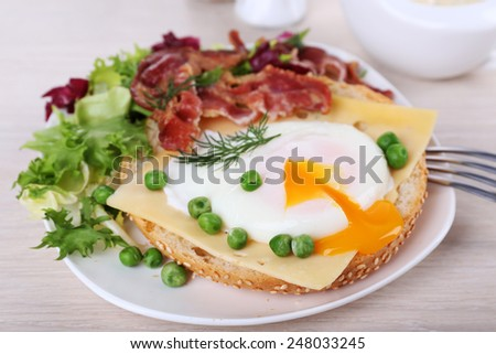 Sandwich with poached egg, cheese and bacon on plate on wooden background - stock photo