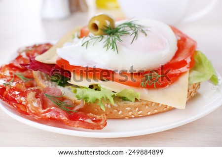 Sandwich with poached egg, tomato and bacon on plate on wooden background - stock photo