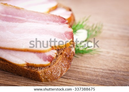 Sandwich with raw bacon on a wooden chopping board - stock photo