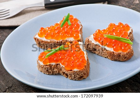 sandwich with red caviar in the form of a heart - stock photo