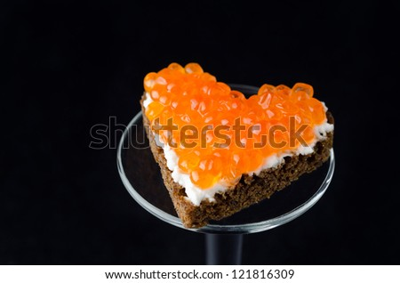 sandwich with red caviar in the form of a heart on a black background