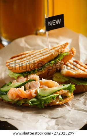 """Sandwich with red fish, cucumbers and lettuce, with a black flag """"new"""" served on a wooden plate with a paper towel, stand near by two glasses of beer on a wooden table, side view - stock photo"""