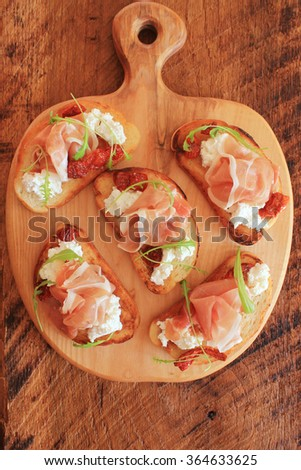 Sandwich with ricotta, prosciutto and tomatoes on cutting board - stock photo