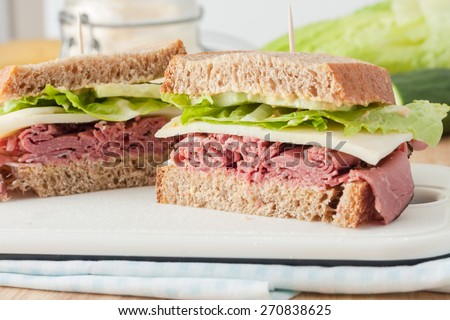sandwich with roast beef pastrami, cheese, mustard and lettuce on whole wheat italian bread on white cutting board - stock photo