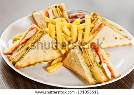 Sandwich with salad, bacon, deep-fried potatoes, pickled cucumber and cheddar sauce - stock photo