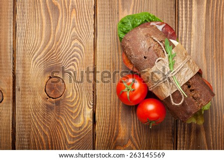 Sandwich with salad, ham, cheese and tomatoes on wooden table. Top view with copy space - stock photo