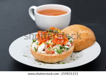 sandwich with salad of cottage cheese, tomato and salmon and cup of black tea, close-up - stock photo