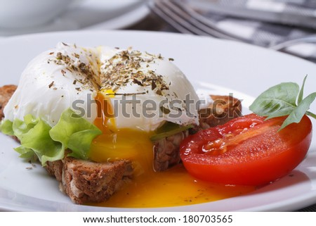 sandwich with salad, open poached egg on a white plate closeup. horizontal  - stock photo