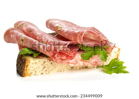 Sandwich with salami sausage and parsley on white background - stock photo