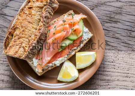 Sandwich with salmon, avocado and tomatoes - stock photo