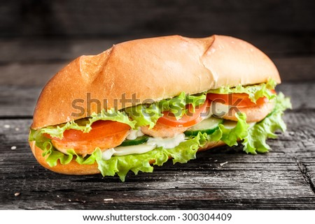 Sandwich with salmon patty and vegetables on a rustic background - stock photo