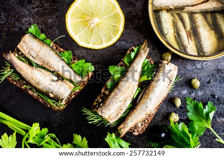 Sandwich with sardines, sprats with parsley and dill - stock photo