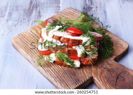 Sandwich with sausage, tomato and mayonnaise on cutting board on color wooden table background - stock photo