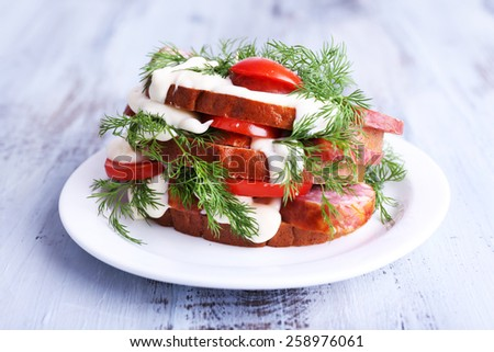 Sandwich with sausage, tomato and mayonnaise on plate on color wooden table background - stock photo