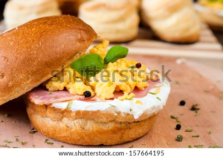 Sandwich with scrambled eggs,ham and white cheese cream.Selective focus on the scrambled eggs - stock photo
