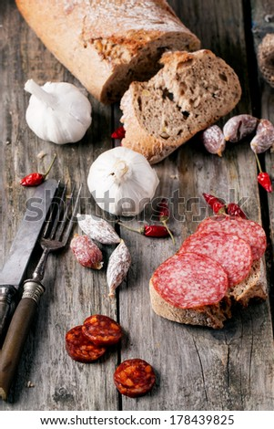 Sandwich with sliced salami served with other sausages, fresh bread, garlic, red hot chili peppers and vintage cutlery on old wooden table. See series - stock photo