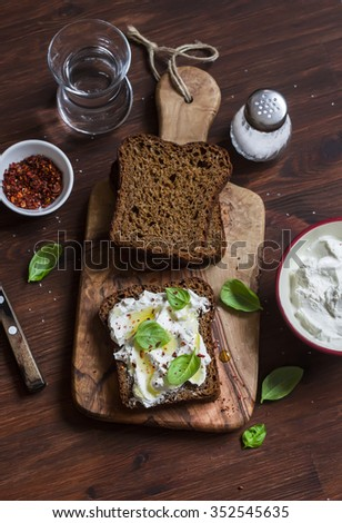 Sandwich with soft cheese, olive oil and basil, served on olive cutting board on dark wooden surface. Healthy Breakfast or snack - stock photo