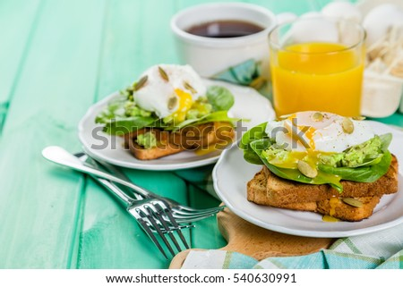 Sandwich with spinach, avocado and egg on wood background
