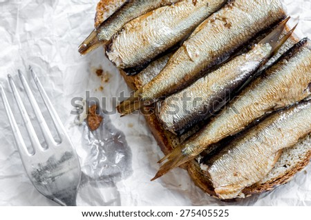 Sandwich with sprats and fork top view close-up