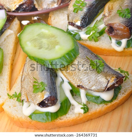 Sandwich with sprats and green cucumber on the board. - stock photo
