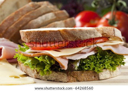 Sandwich with Swiss cheese, ham, tomato and curly lettuce, on crusty fresh-sliced bread. - stock photo