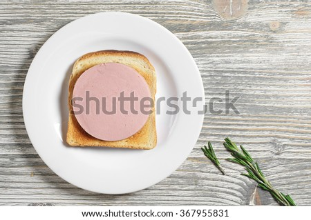 Sandwich with toasted bread and boiled sausage on old wooden table, top view