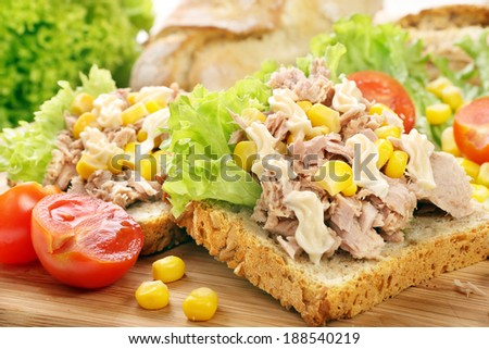 Sandwich with tuna, corn and mayonnaise on wood background - stock photo
