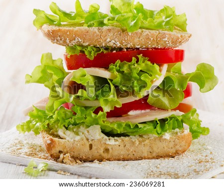 Sandwich with turkey and fresh vegetables on a wooden background  - healthy eating