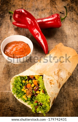 Sandwich wrap and salsa sauce on a wooden table. Selective focus in the middle of sandwich.