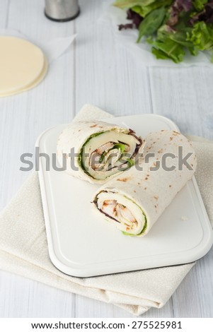 sandwich wrap or tortilla with leftover meat, cheese and lettuce on white chopping board, vertical image - stock photo