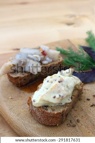 Sandwiches of rye bread and herring. Pieces of fish are herring on bread. Sandwiches with bread and fish on a wooden boards background. Traditional appetizer Scandinavian.                            - stock photo