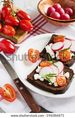 sandwiches of rye bread, cheese, tomato and radish. selective focus