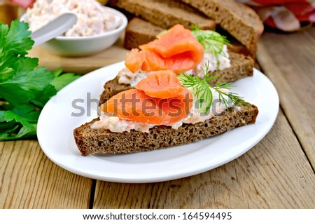 Sandwiches on two pieces of rye bread with cream, dill, cucumber and salmon in a white plate on a wooden boards background - stock photo