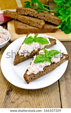 Sandwiches on two pieces of rye bread with cream of salmon and mayonnaise, basil, napkin, parsley on a wooden boards - stock photo