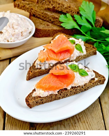 Sandwiches on two triangular pieces of rye bread with cream, basil and salmon, knife, napkin, parsley on a wooden boards background - stock photo