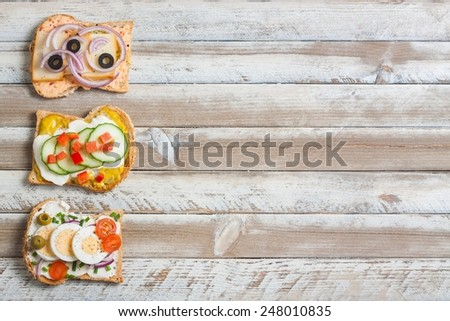 Sandwiches on wooden background, empty space on right. - stock photo